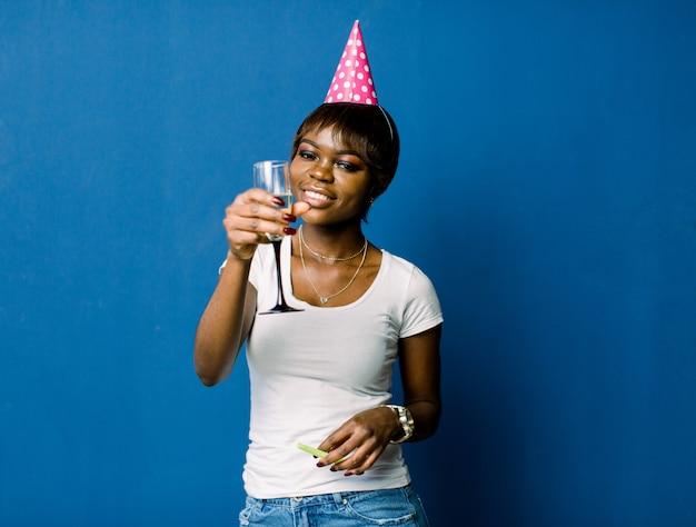 Feier und party. spaß haben. junge hübsche afrikanische frau im weißen t-shirt und in den jeans und im geburtstagshut lacht. buntes studioporträt mit blauem raum.