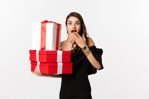 Feier- und weihnachtsfeiertagskonzept. frau, die weihnachtsgeschenke hält und überrascht schaut, erhält geschenke und steht über weißem hintergrund.