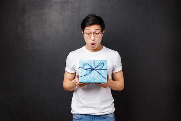 Feier, urlaub und lifestyle-konzept. überrascht und aufgeregt erhält ein erstaunter asiatischer typ eine geschenkbox, hält ein geschenk und schaut es amüsiert an. er hat nicht erwartet, dass sich ein mitarbeiter an den geburtstag erinnert