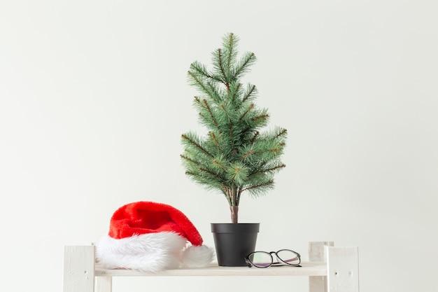 Feier, winterferien und werbekonzept - kleiner weihnachtsbaum und weihnachtsmütze über weißer wand.