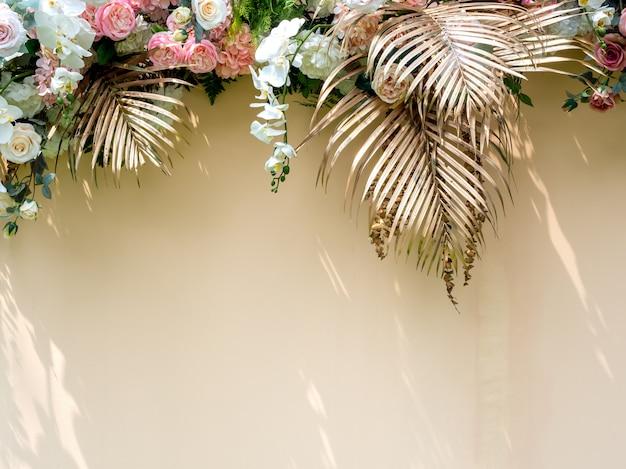 Feierdekoration mit goldenen tropischen palmblättern mit blumenstrauß der weißen und rosa rosen.