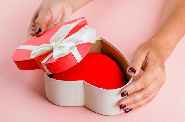 Feierkonzept auf der hohen winkelansicht des rosa tisches. frau öffnet geschenkbox.