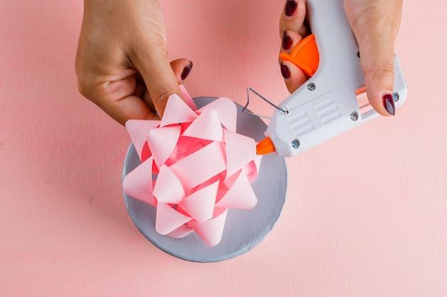 Feierkonzept mit geschenkbox auf rosa tisch flach legen. frau mit klebepistole.