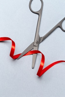 Feierliche eröffnung mit einer schere und einem roten band auf einem grauen hintergrund