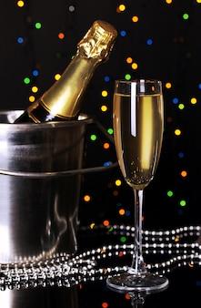 Feierlicher champagner mit weinglas auf der oberfläche der weihnachtsbeleuchtung