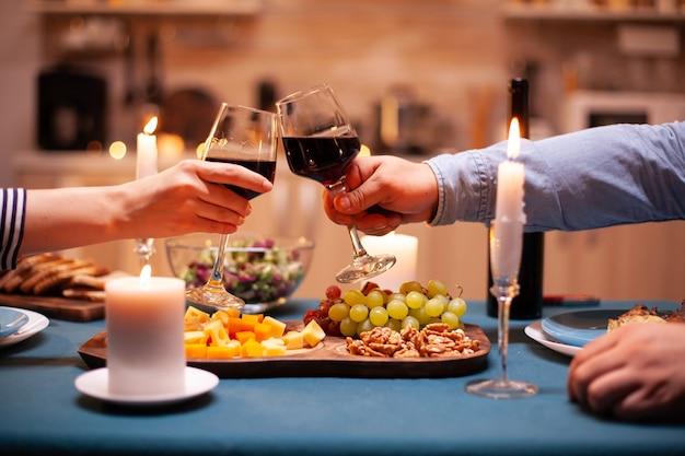 Feiern des jubiläums des jungen paares in der küche, das mit rotweingläsern klirrt. fröhliches, fröhliches junges paar, das zusammen in der gemütlichen küche diniert und das essen genießt.