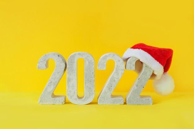 Feiern des neuen jahres 2022. konkrete ziffer 2022 in weihnachtsmütze auf gelbem hintergrund.