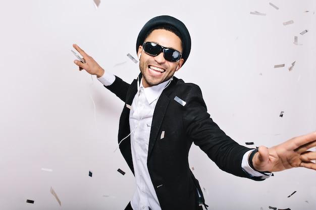 Feiern karaoke-party von aufgeregten gutaussehenden mann in anzug, hut, schwarze sonnenbrille, die spaß in lametta hat. modischer look, gesang, tänzer, glück, ausdruck, musik, genießen.