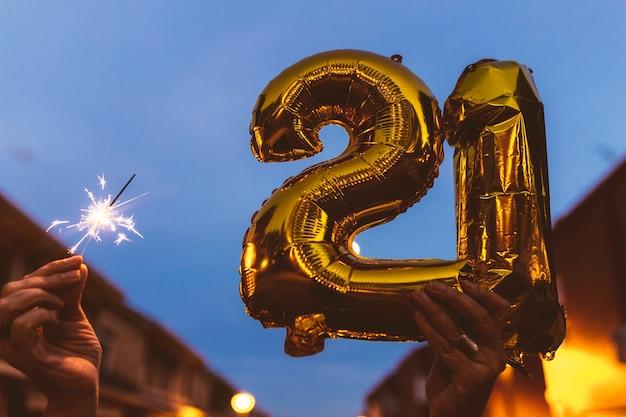 Feiern mit goldfolienballons nummer 21 und wunderkerze in der nacht. frohes neues jahr 2021 feiern.