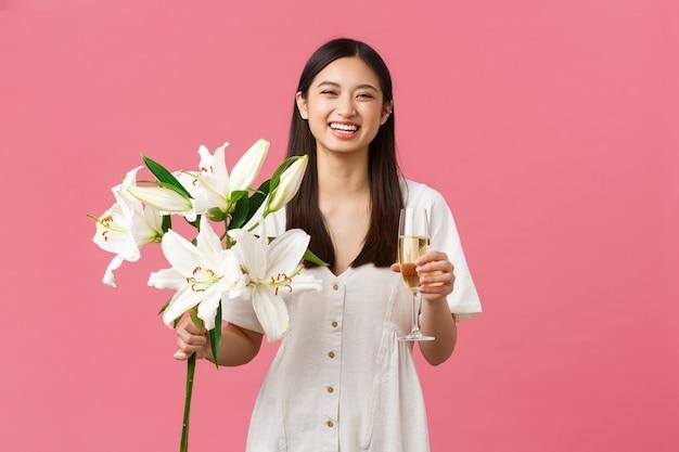 Feiern, partyferien und lustiges konzept. dummes alles gute zum geburtstagsmädchen im weißen kleid, breit lächelnd, während es einen schönen blumenstrauß aus lilien erhält, ein glas champagner hält und rosa hintergrund steht