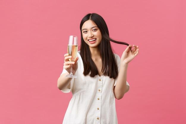 Feiern, partyferien und lustiges konzept. flirty und kokette junge frau mit glas-champagner, die versucht, den kerl beim feiern des ereignisses zu verführen, albern zu lachen und zu lächeln und prost zu sagen.