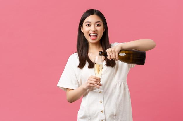 Feiern, partyferien und lustiges konzept. fröhliche sorglose asiatische frau im urlaub, champagner in glas gießen und lachen, wochenende oder freizeit genießen, rosa hintergrund stehen.