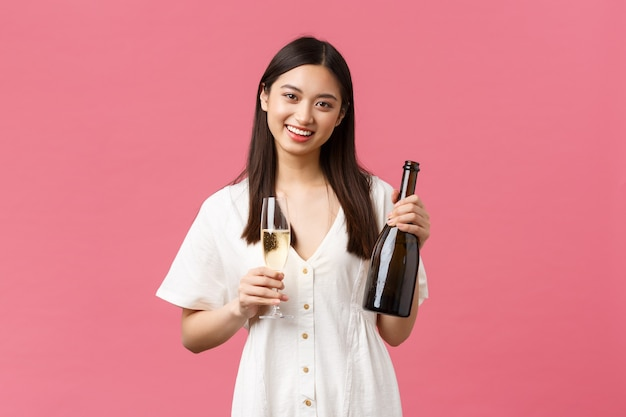 Feiern, partyferien und lustiges konzept. fröhliches, gut aussehendes, stilvolles asiatisches mädchen, das während des feierns toast vorschlägt, flasche champagner und glas hält, rosa hintergrund