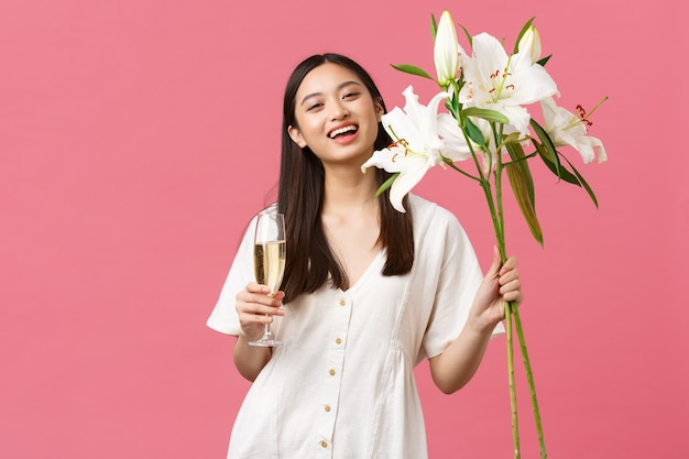 Feiern, partyferien und lustiges konzept. hübsche junge frau mit glaschampagner und lilienstrauß, die ihren geburtstag feiert und mit b-day, rosa hintergrund gratuliert wird.