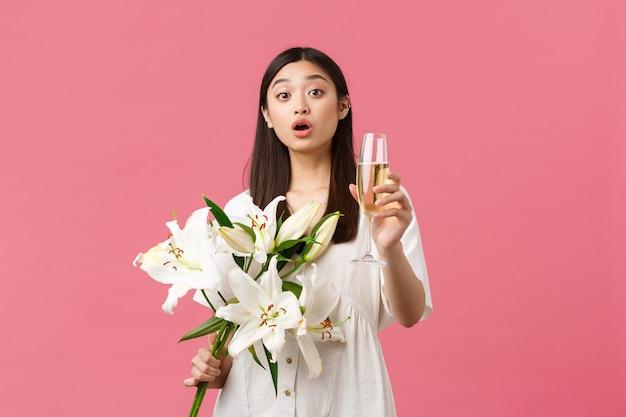 Feiern, partyferien und lustiges konzept. lächelnde hübsche glamouröse asiatische frau im kleid mit weißem lilienblumenstrauß, glas champagner erhebend, um toast zu machen, getränk für geburtstagsmädchen