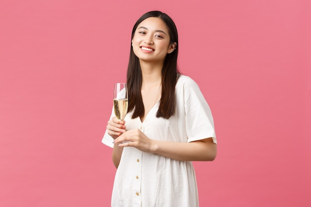 Feiern, partyferien und lustiges konzept. lächelndes glückliches geburtstagsmädchen im weißen kleid, das das feiern mit freunden genießt und glaschampagner über rosafarbenem hintergrund hält. platz kopieren