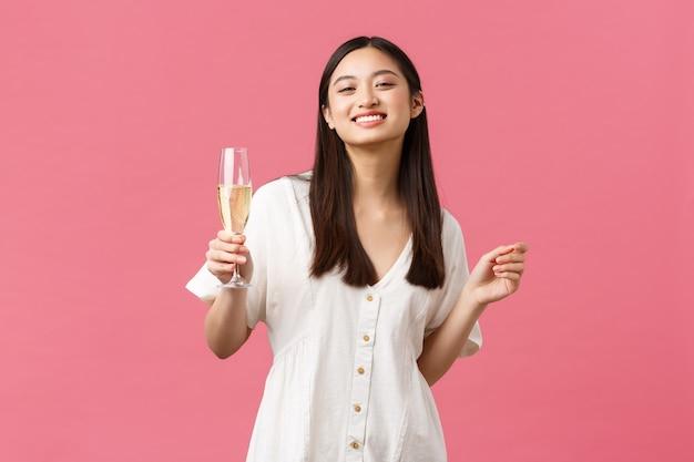 Feiern, partyferien und lustiges konzept. lächelndes glückliches geburtstagsmädchen im weißen kleid, das das feiern mit freunden genießt und glaschampagner über rosafarbenem hintergrund hält.