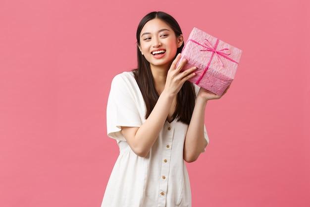 Feiern, partyferien und lustiges konzept. neugierige süße aufgeregte frau im weißen kleid, die geburtstag feiert, wundert sich, was im b-day-geschenk ist, schütteln die schachtel und lächeln glücklich, rosa hintergrund