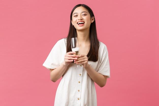 Feiern, partyferien und lustiges konzept. schönes lächelndes und lachendes asiatisches mädchen, das sich auf der veranstaltung unterhält, ein glas champagner hält, den abend genießt, rosa hintergrund.