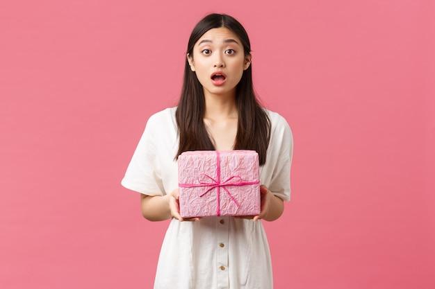 Feiern, partyferien und lustiges konzept. überraschtes und berührtes glückliches asiatisches mädchen, das verwundert den mund öffnet, als unerwartetes geschenk erhält, kamera dankbar schaut, geschenkbox hält.