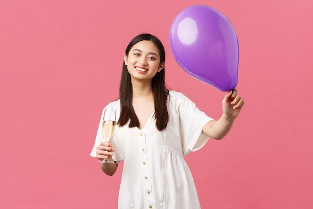 Feiern, partyferien und lustiges konzept. zarte hübsche asiatische frau in weißem kleid, ballon und glas champagner halten, toast während der veranstaltung machen, gastgeber gratulieren, rosa hintergrund.