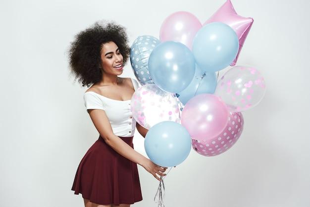 Feiern sie geburtstag wunderschöne afroamerikanische frau mit lockigem haar, die bunte luftballons hält, während