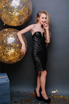 Feiern sie glückliche partei der freudigen erstaunlichen jungen frau mit langen blonden lockigen haaren, im schwarzen luxuskleid, das spaß mit großen luftballons voll mit goldenen lametta hat.