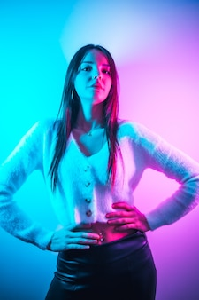 Feiern sie in einem nachtclub mit rosa blauen neonlichtern, ein junger brünetter kaukasier, der spaß in einem weißen wollpullover hat