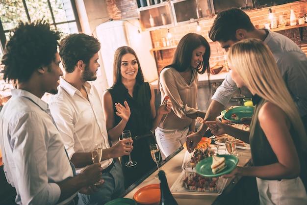 Feiern sie mit den besten freunden. gruppe fröhlicher junger leute, die eine heimparty mit snacks und getränken genießen, während sie in der küche kommunizieren communicating