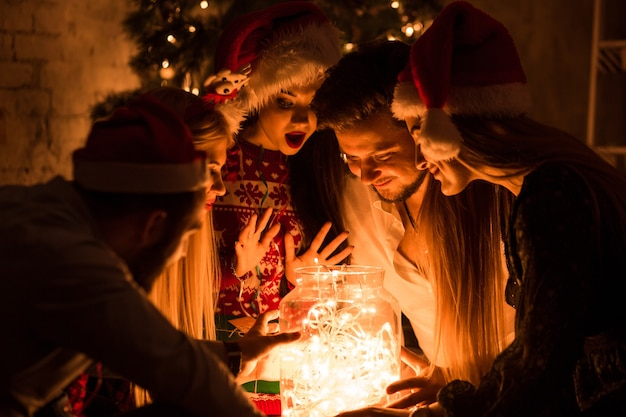 Feiern und feiern. winterurlaub und weihnachten. girlande auf glas als dekoration. junge leute und girlande.
