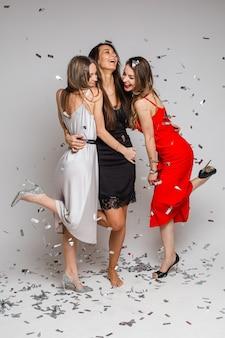Feiern von jungen freundinnen, die abendkleider tragen, die unter silbernem konfetti auf feiertagsfeier auf grauem hintergrund umarmen