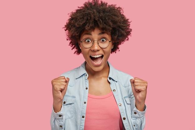 Feiern wir meinen erfolg! attraktive lockige dunkelhäutige frau hebt geballte fäuste, freut sich über triumph oder sieg, trägt eine runde brille und eine jeansjacke, fühlt sich begeistert und amüsiert, isoliert an der rosa wand