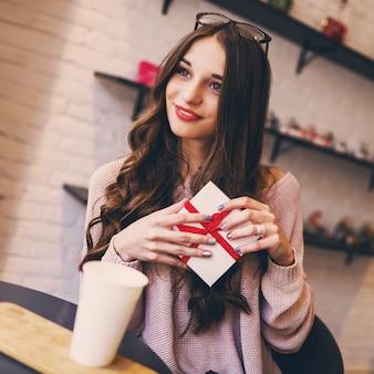 Feiernde frau im stilvollen modernen café mit geschenken, die ihren geburtstag oder datierung genießen.