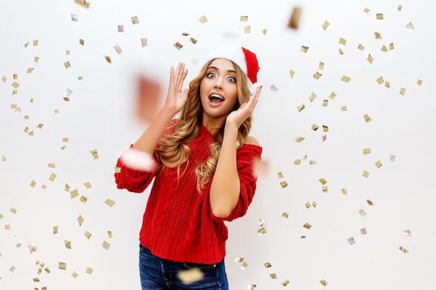 Feiernde mädchen in santa maskerade hut haben spaß in konfetti auf weißer wand. neue ohrparty-stimmung. gemütlicher roter pullover. wahre emotionen. überraschen sie verrückte emotionen.