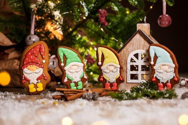 Feiertag traditionelles essen bäckerei, lebkuchen kleine märchen-zwerge in gemütlicher dekoration mit girlandenlichtern