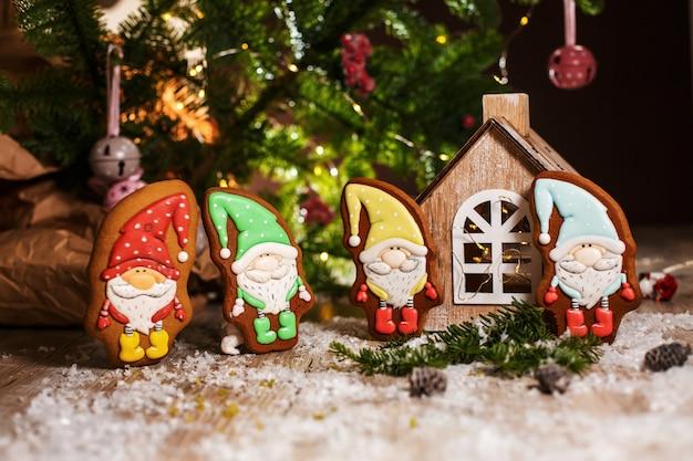 Feiertag traditionelles essen bäckerei. vier kleine märchenhafte lebkuchenzwerge in gemütlicher dekoration mit girlandenlichtern