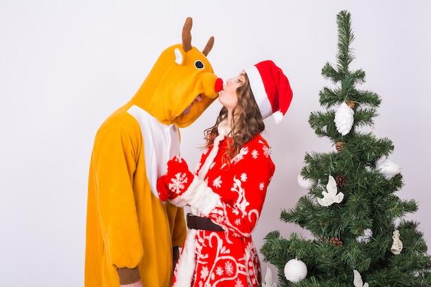 Feiertag, weihnachten und lustiges konzept - schöne frau im weihnachtsmannkostüm, das mann im hirschkostüm auf weißem hintergrund küsst.