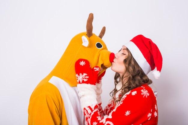 Feiertag, weihnachten und lustiges konzept - schöne frau im weihnachtsmannkostüm, die mann im hirschkostüm auf weißer oberfläche küsst