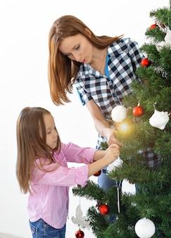 Feiertage, eltern und feierndes konzept - glückliche familie, die einen weihnachtsbaum mit kugeln im wohnzimmer auf weißem hintergrund schmückt.