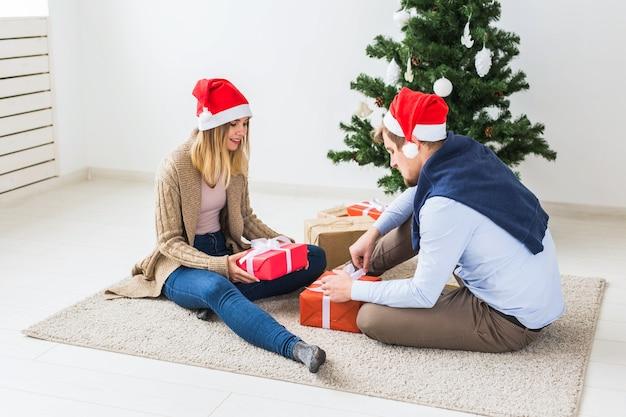 Feiertage, familie und festliches konzept - paar mit weihnachtsgeschenken zu hause