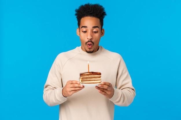 Feiertage, feierkonzept. fröhlicher afroamerikaner-b-day-typ, der geburtstag feiert, kuchen hält und kerze ausbläst, wunsch, stehenden blauen hintergrund freudig stehend, feiert