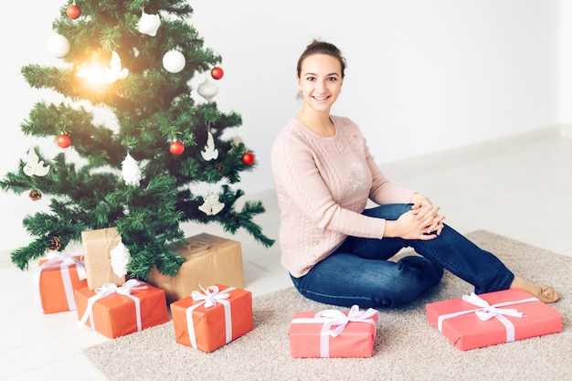 Feiertage, feiern und festliches konzept - schöne junge frau, die unter weihnachtsbaum sitzt