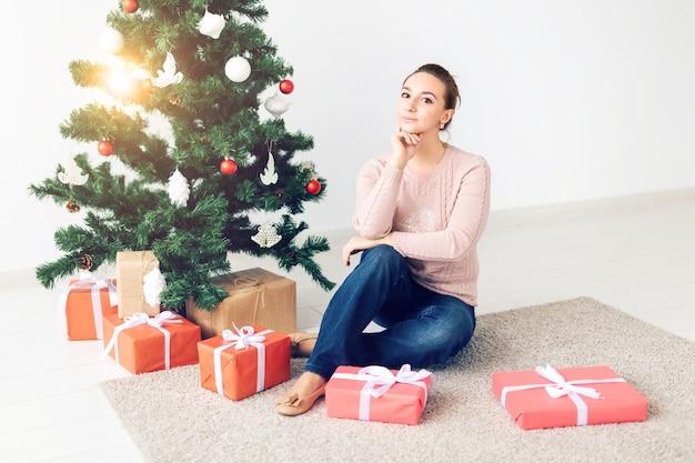 Feiertage, feiern und festliches konzept - schöne junge frau, die unter weihnachtsbaum sitzt Premium Fotos