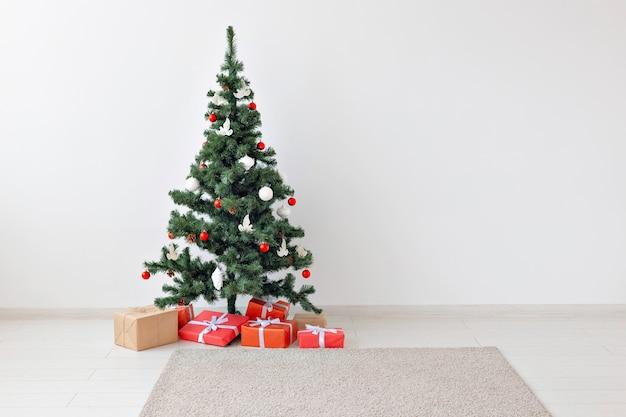 Feiertage, feiern und geschenke konzept - weihnachtsbaum und viele geschenkboxen auf weiß drinnen mit kopierraum.