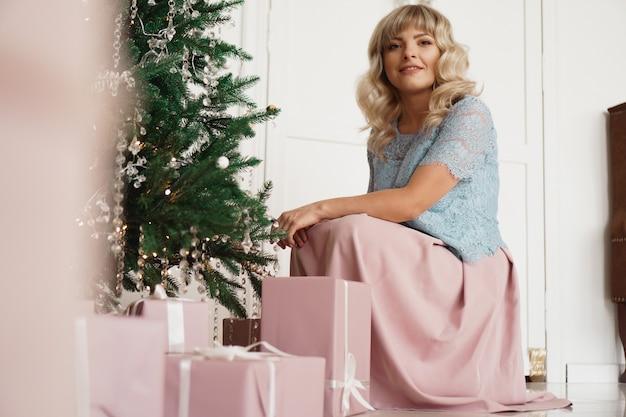 Feiertage, feiern und leutekonzept - junge frau im eleganten kleid über weihnachtsinnenhintergrund