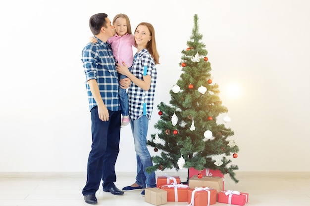 Feiertage, geschenke und weihnachtsbaumkonzept - kleine familie, die an weihnachten eine glückliche zeit zusammen hat