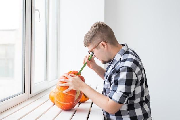 Feiertage, halloween, dekoration und menschenkonzept - nahaufnahme eines mannes mit kürbissen, die sich auf halloween vorbereiten.