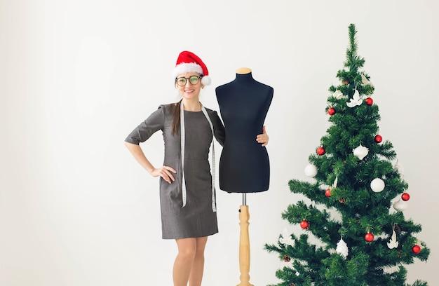 Feiertage, kleidungsdesign und geschenkkonzept - weibliche kleidungsdesignerin nahe weihnachtsbaum, weihnachten im schneideratelier.
