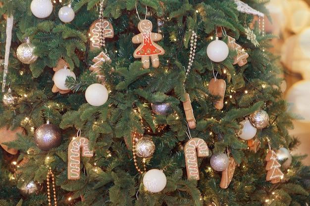 Feiertage, neujahr, dekoration und feierkonzept - nahaufnahme des mit bällen und spielzeug geschmückten weihnachtsbaums