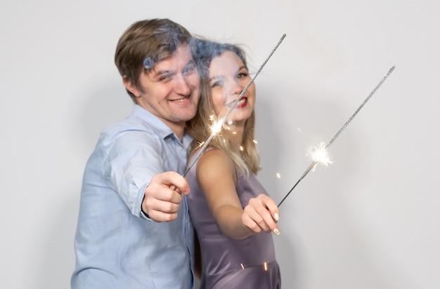 Feiertage, neujahr, weihnachten und feiern konzept - junges paar umarmt mit gekreuzten bengals licht oder wunderkerzen auf weißem hintergrund
